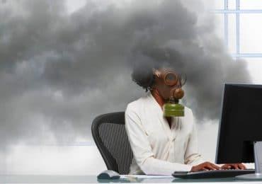 Black businesswoman wearing gas mask at smoking computer