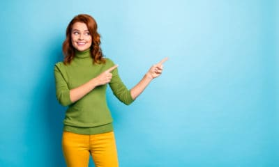 A Woman Pointing at a Blue Wall